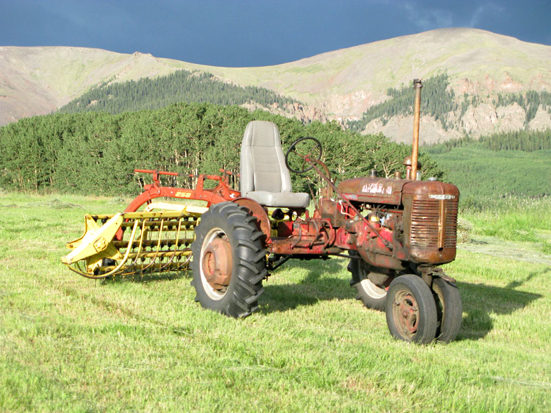 Antique Farmall Tractor with Rake in Moutain Hay Meadow